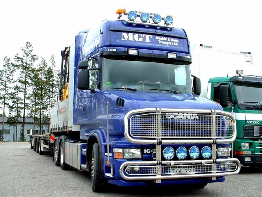 Scania azul con remolque para vehiculos pesados